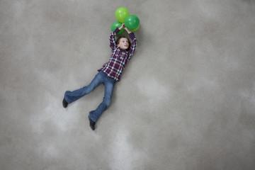Mädchen hält Ballons auf grauem Hintergrund