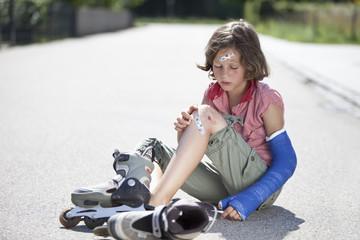 Deutschland, Bayern, Verletztes Mädchen sitzedn auf der Straße nach Inline-Skating Unfall