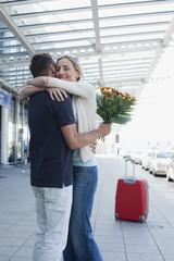 Deutschland, Leipzig-Halle, Flughafen, Paar umarmt sich, Mann hält Blumen