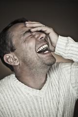 Nahaufnahme von reifen Mann, der lustige Gesichter vor schwarzem Hintergrund macht, lachen