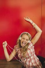 Deutschland, München, Teenager-Mädchen hören Musik im Café