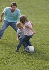 Vater spielt Fußball mit Kindern