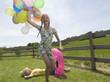 Mädchen mit Luftballons, springt über Jungen