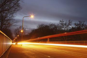 Brücke bei Nacht mit Autoscheinwerfer