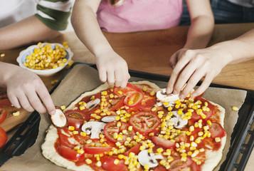 Deutschland, Köln, Mutter und Kinder garnieren Pizza