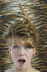 Junge Frau mit Kunststoff-Giraffe im Haar blickt schockiert nach oben