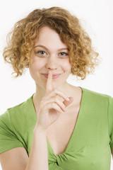 Junge Frau mit Finger auf Lippen