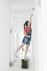 Deutschland, Köln, Junge Frau auf Kiste, streicht mit Pinsel Rolle im Korridor