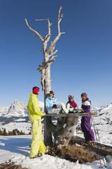 Italien, Trentino-Alto Adige, Südtirol, Bozen, Seiser Alm, Menschen ruhen nahe Kahler Baum auf verschneiten Landschaft