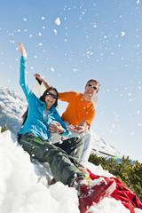 Österreich, Salzburg Land, Altenmarkt-Zauchensee, Paar mittleren Alters sitzt im Winter im Schnee