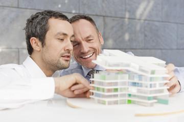 Deutschland, Leipzig, Geschäftsleute diskutieren über Architekturmodell