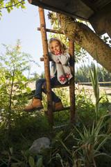 Österreich, Salzburg, Flachau, Mädchen auf einer Leiter in Bauerngarten, Lächeln