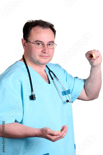 doctor holding small yellow pill