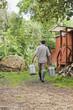 Bauer trägt Milchkannen, Rückansicht