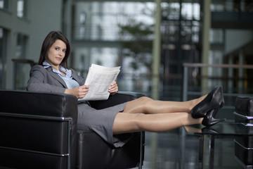 Deutschland, Bayern, Geschäftsfrau mit Zeitung, Lächeln