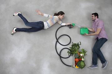 Mann hält Benzinkanister, Frau tankt Kraftstoff