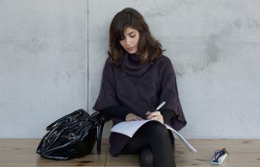 Deutschland, Leipzig, junge Frau sitzt und schreibt in ein Heft