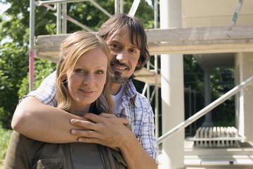 Junges Paar umarmt sich vor Haus im Bau