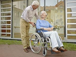 Deutschland, Köln, Alter Mann schiebt Frau im Rollstuhl