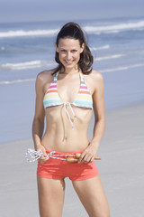 Junge Frau am Strand mit Springseil