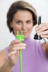 Frau hält grünen und schwarzen Stecker
