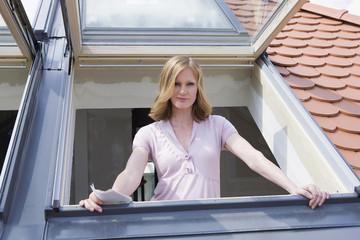 Junge Frau steht am Fenster