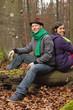 Deutschland, Berlin, Wandlitz, Paar sitzt auf Baumstamm, Lächeln