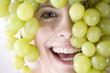 Junge Frau mit Weintraube über dem Kopf, lächelt