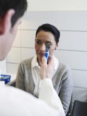 Deutschland, Hamburg, Arzt untersucht Augen des Patienten mit Otoskop