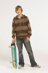 Teenager  stehend mit Skateboard über dem Kopf und lächelnd