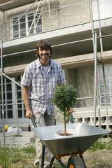 Junger Mann auf der Baustelle, schiebt Schubkarre mit Pflanzen