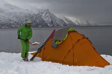Norwegen, Skier Entfernen von Schnee mit Schaufel in der Nähe von Zelt