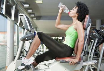 Deutschland, Bayern, Frau im Fitness-Studio trinkt Wasser, Seitenansicht