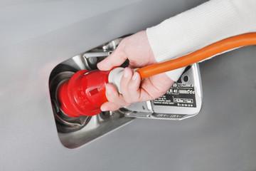 Hand einer Frau an Hochspannungskabel, Elektroauto laden