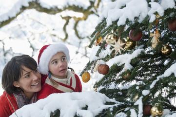 Österreich, Land Salzburg, Flachau, Junge Mutter und Tochter Blick auf Weihnachtsbaum