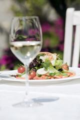 Italien, Südtirol, Gemischter Salat auf Teller mit einem Glas Weißwein