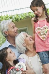 Deutschland, Bayern, Großeltern mit Enkelin hält Lebkuchen