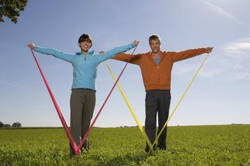 Junges Paar trainigert mit Gummiband