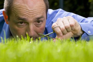 Deutschland, Baden-Württemberg, Stuttgart, Mann schneidet Gras mit Schere