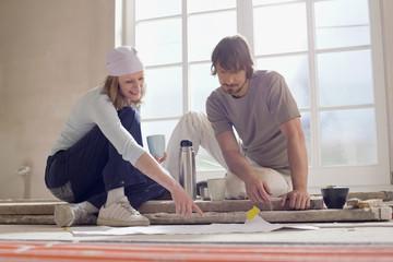 Junges Paar sitzt auf Boden eines leeren Raumes, schauen in Bauplan