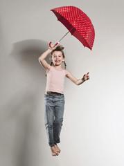 Mädchen springt mit Sonnenschirm, Lächeln