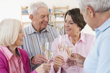Deutschland, Leipzig, Ältere Männer und Frauen trinken Sekt, lächeln