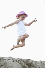 Deutschland, Mädchen springend auf Sanddüne
