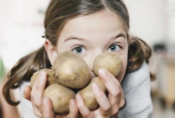 Deutschland, Köln, Mädchen hält Kartoffeln