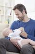 Deutschland, Bayern, München, Vater Fütterung Milch Baby im Wohnzimmer