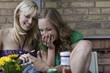 Deutschland, Berlin, zwei Frauen mit Handy, albern herum