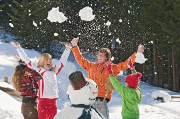 Österreich, Salzburger Land, Altenmarkt, Familie vor Schneemann, werfen Schnee in die Luft, lachen