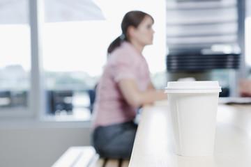 Deutschland, Köln, Plastikbecher im Vordergrund, Frau sitzt im Hintergrund, im Café