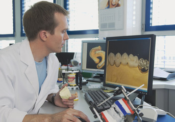 Deutschland, Nürnberg, Junge Zahntechniker arbeitet am Computer