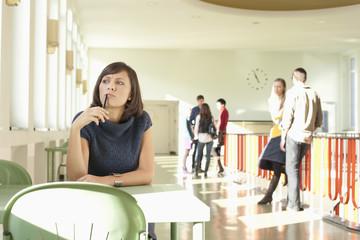 Deutschland, Leipzig, Frau sitzt am Tisch und denkt nach, Studenten stehen im Hintergrund